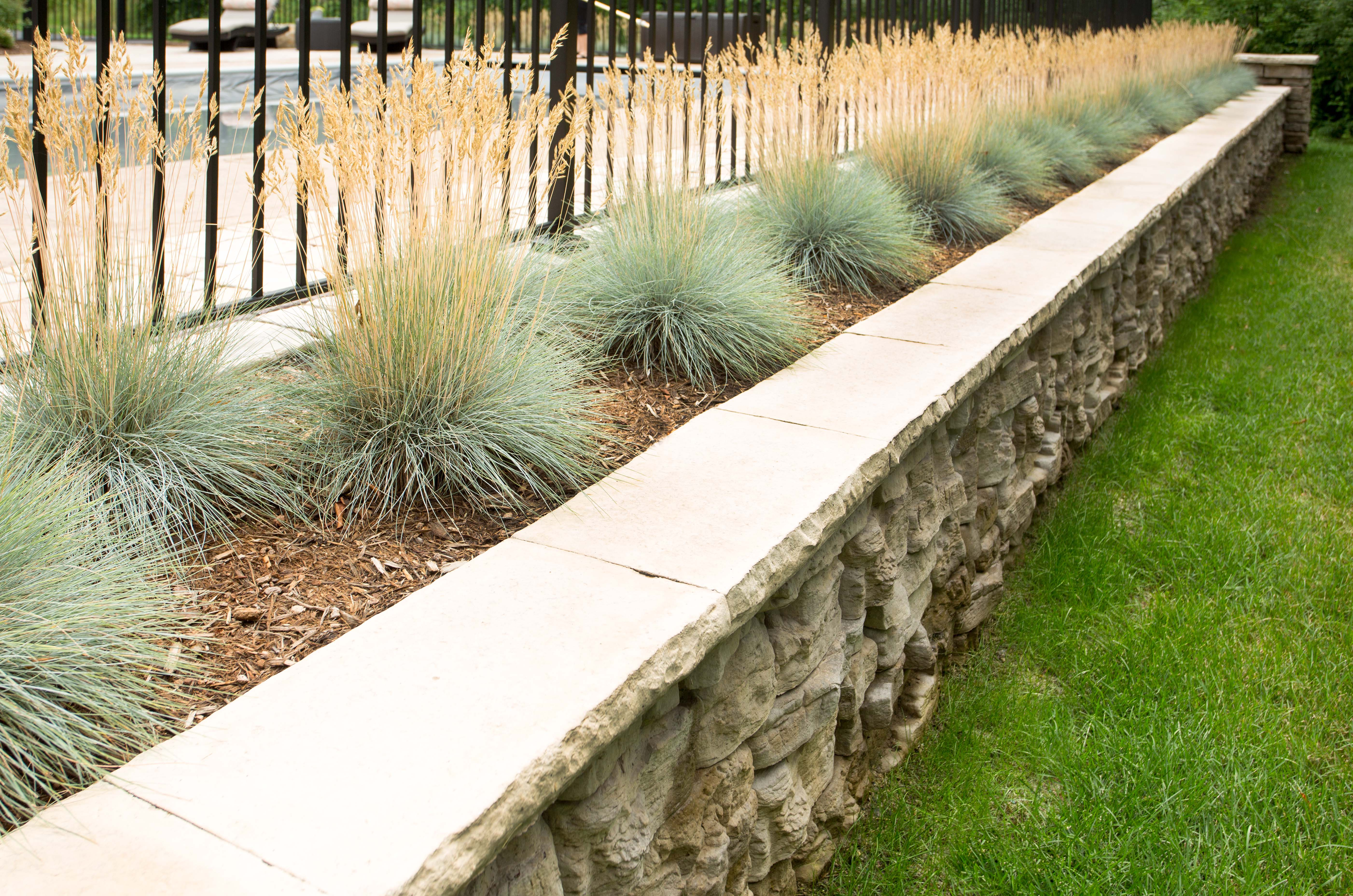 Concrete retaining wall with landscaping and a fence