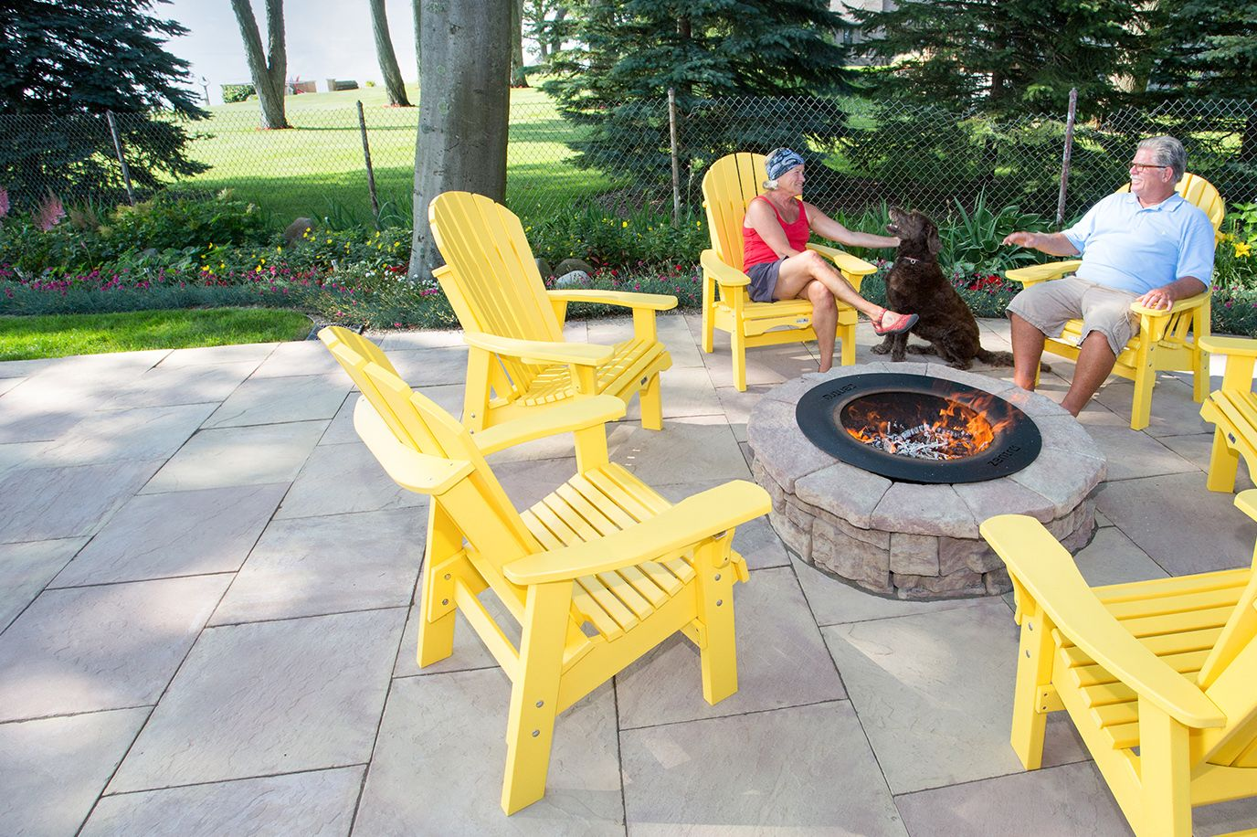Couple with their dog enjoying a fire in a Belvedere Fire Pit