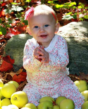 Baby sitting in bushel of apples