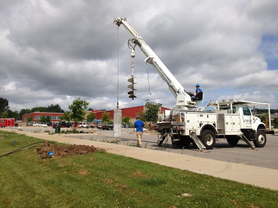 Installing precast light pole bases with an auger