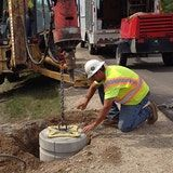 Rauhorn Electric places a Pole Base at grade with a lifting plate
