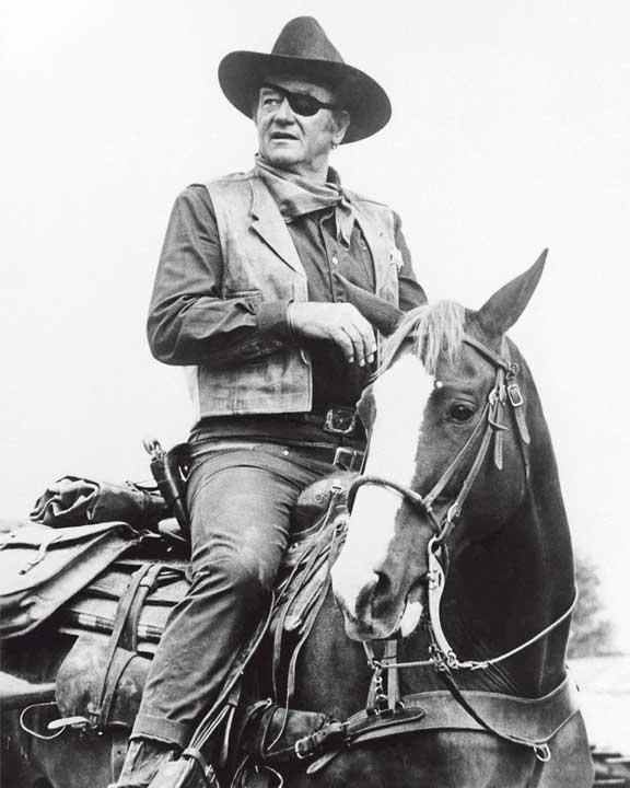 John Wayne riding a horse