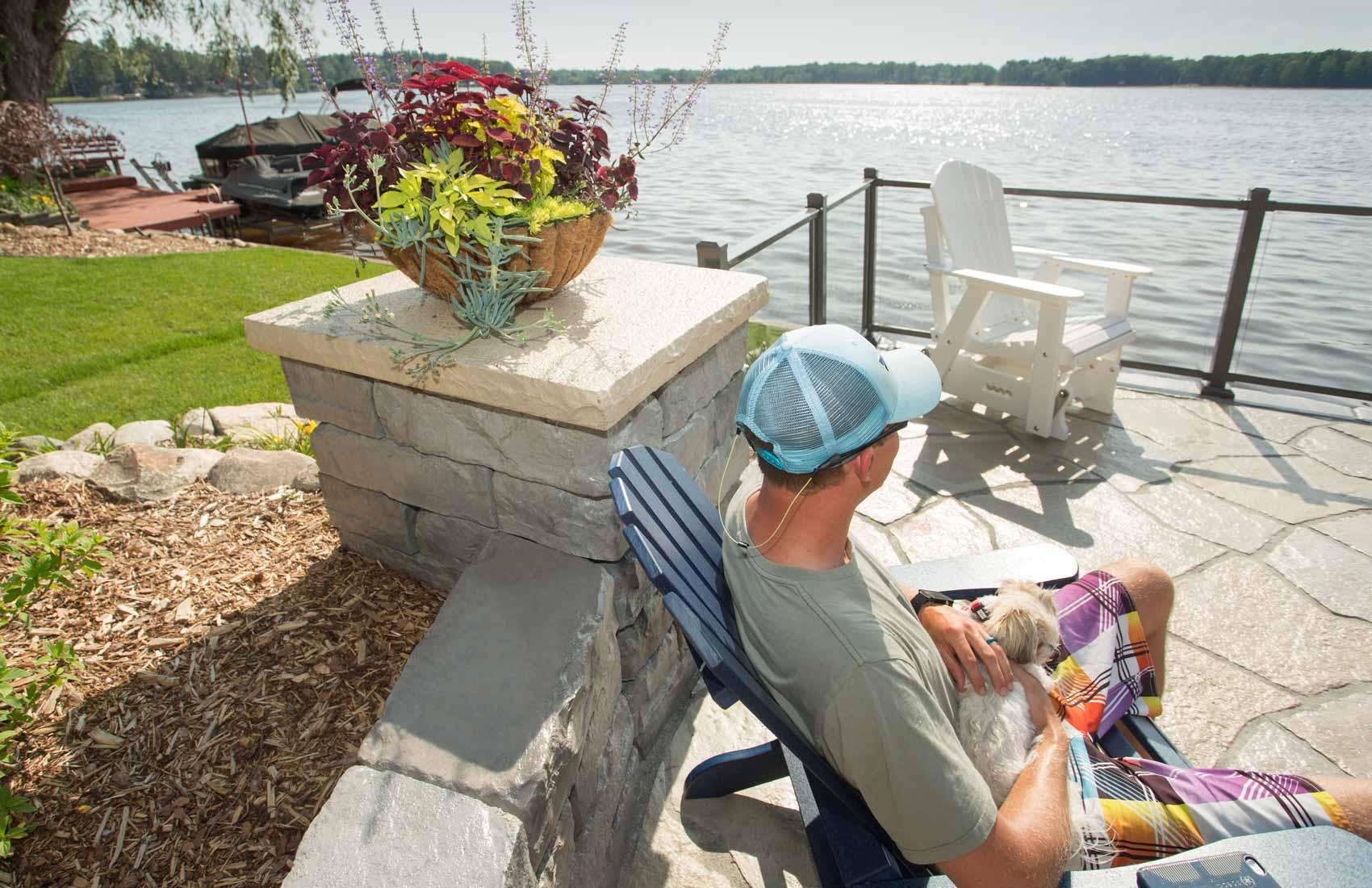 Man looking at lake next to Kodah wall and column with Grand Flagstone pavers