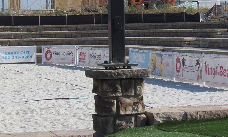 Ledgestone light pole base for volleyball court