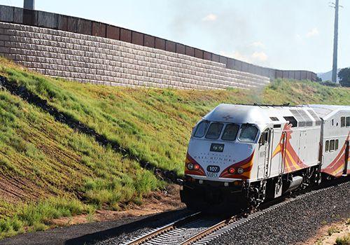Rail Runner trail moves past fenced Limestone retaining wall