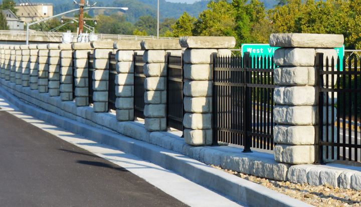 Redi-Rock Columns hold up wrought iron fence