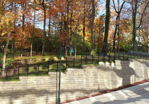 Ledgestone retaining wall with black fence