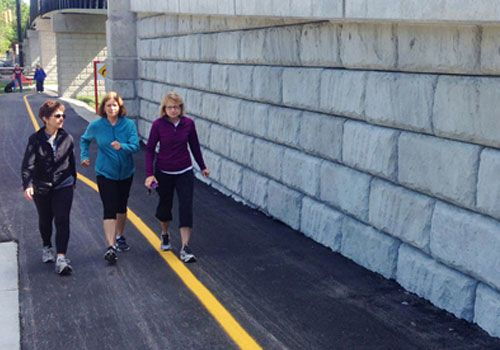 Three woman walk on a paved trail adjacent to a retaining wall