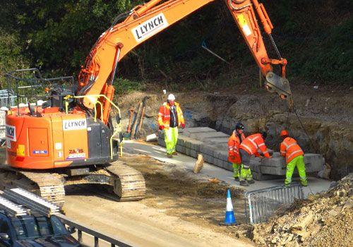 A small crew installs precast modular blocks along smart motorway