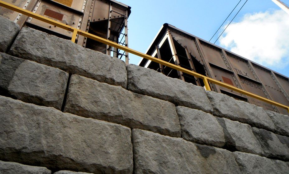 Limestone texture wall with train passing overhead