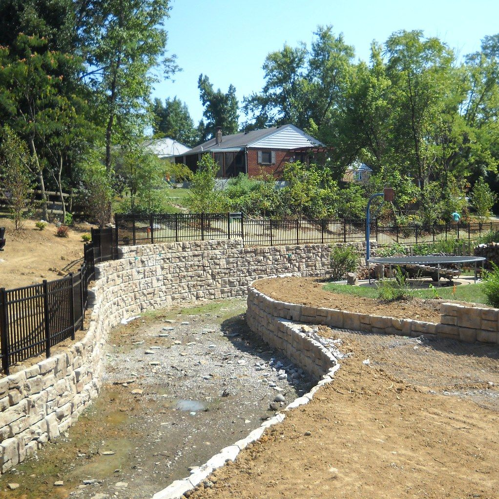 Curved Ledgestone gravity wall provides storm channel support