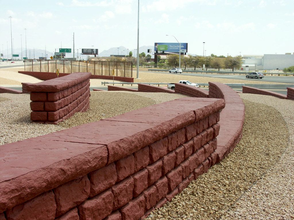 Freestanding walls with caps and red coloring along freeway