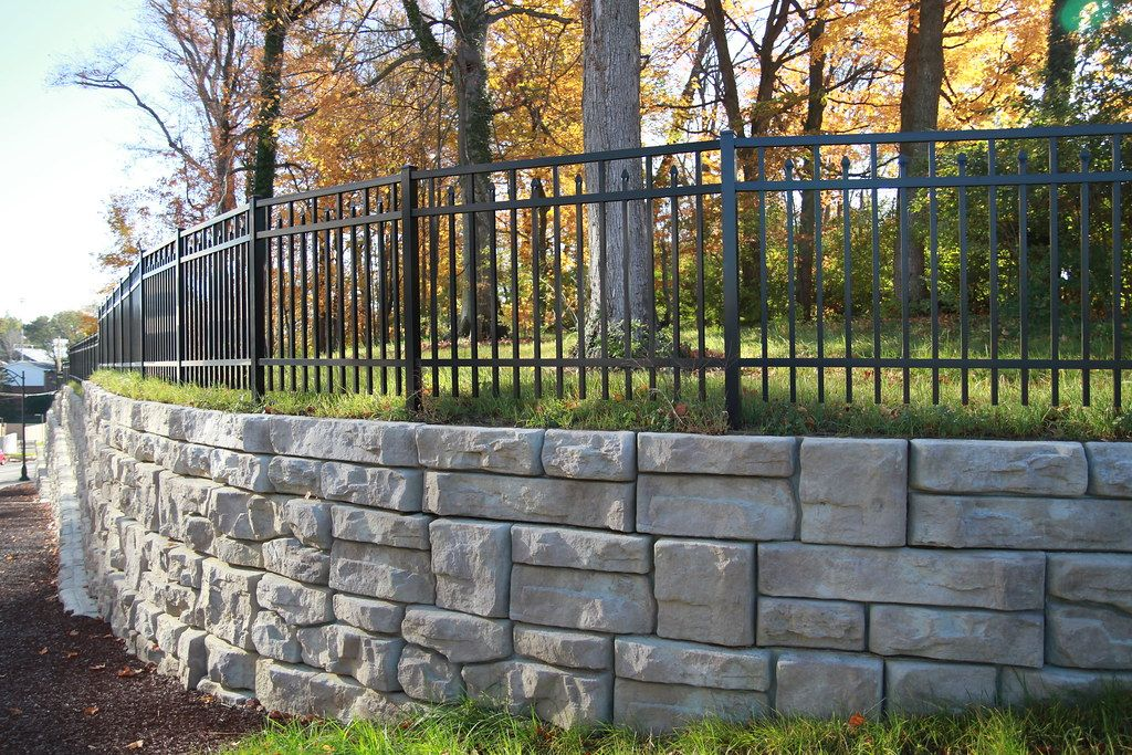 Curved Ledgestone wall with black fencing