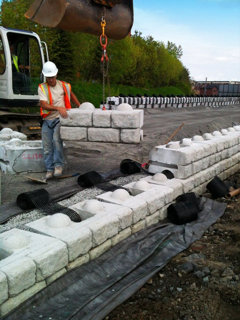 Construction worker guiding a retaining wall block into place