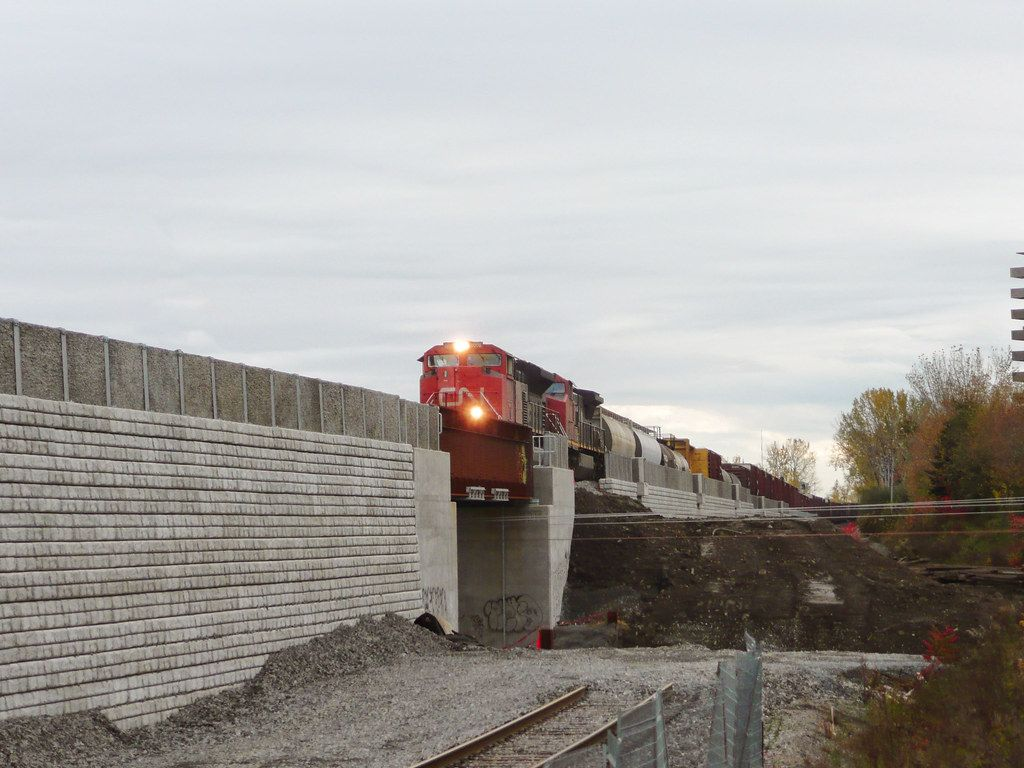 CN Rail train running on elevated track supported by reinforced retaining wall