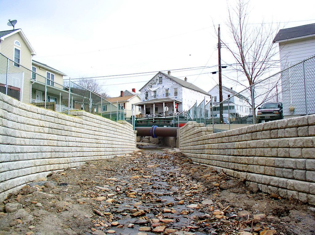 RCobblestone flood walls with fencing line the Coal Creek storm channel