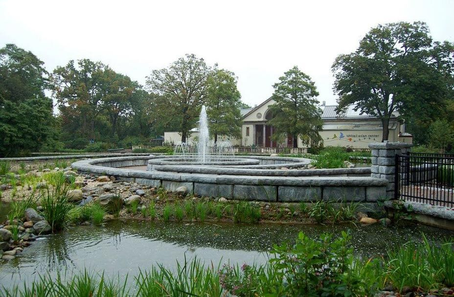 Curving freestanding walls in limestone texture ring a fountain at the Philadelphia Zoo