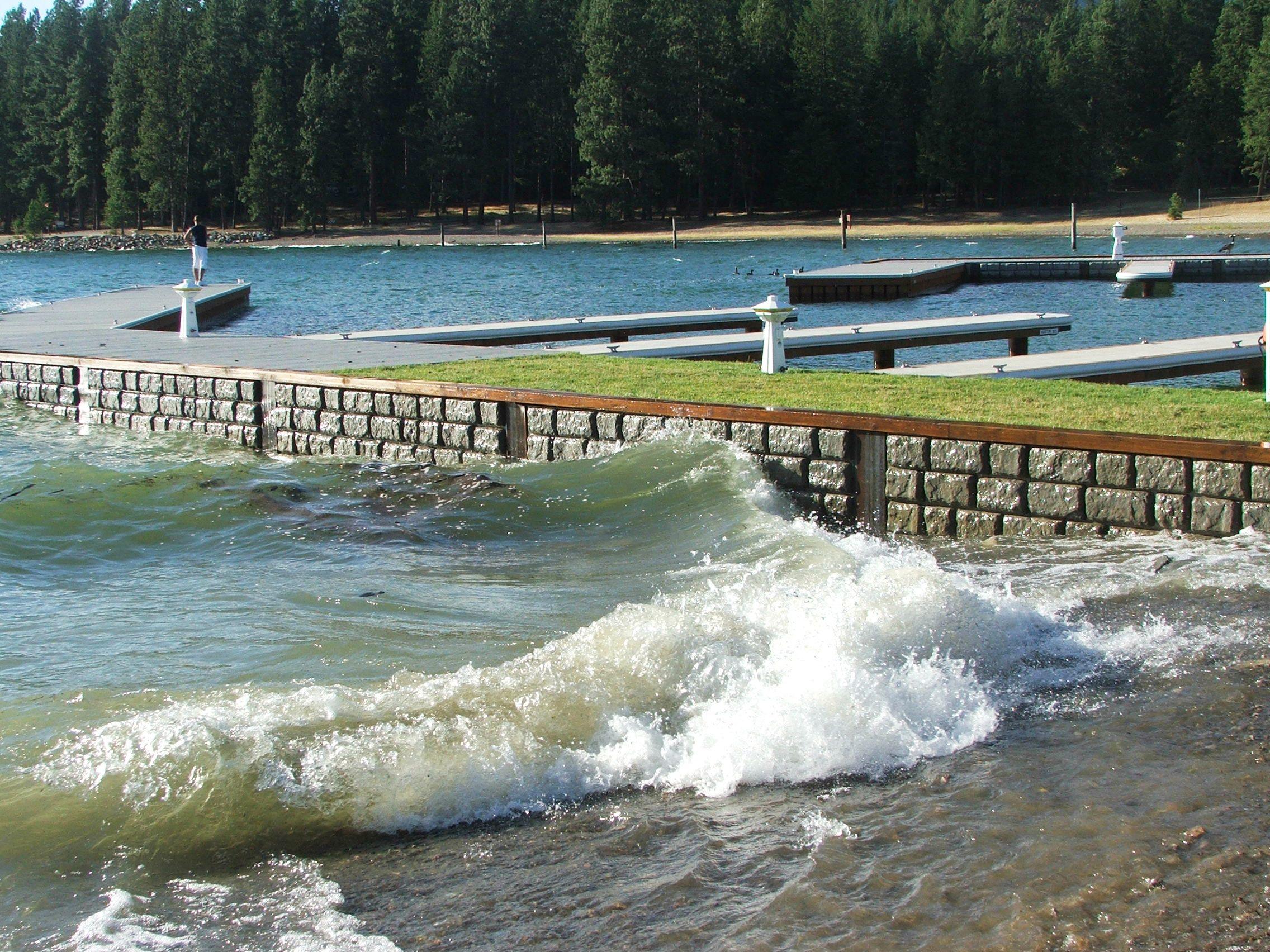 Waves spash against a marina sea wall
