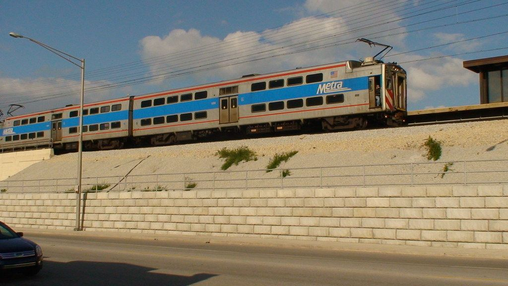 A Metra commuter train goes by with a Limestone retaining wall providing support below