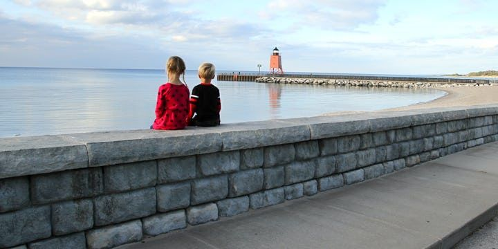 Two kids sit on a Cobblestone texture seat wall looking out at lake and lighthouse