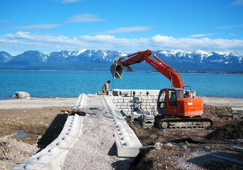 A crew installs Redi-Rock in a remote mountain lakeside location