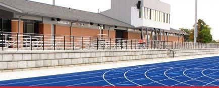 Blue running track with freestanding limestone wall in front of bleachers