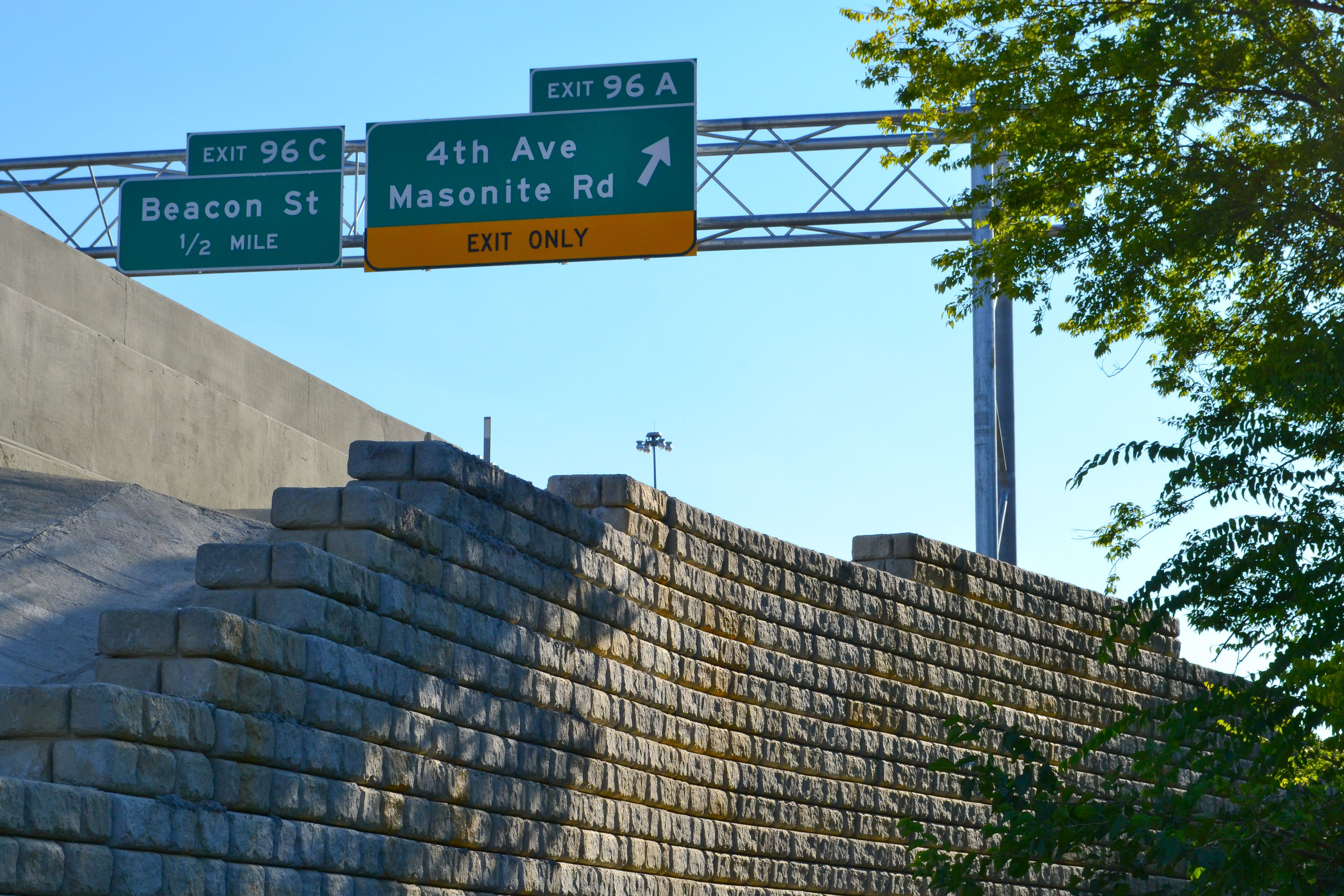 Tall Cobblestone retaining wall with highway signs