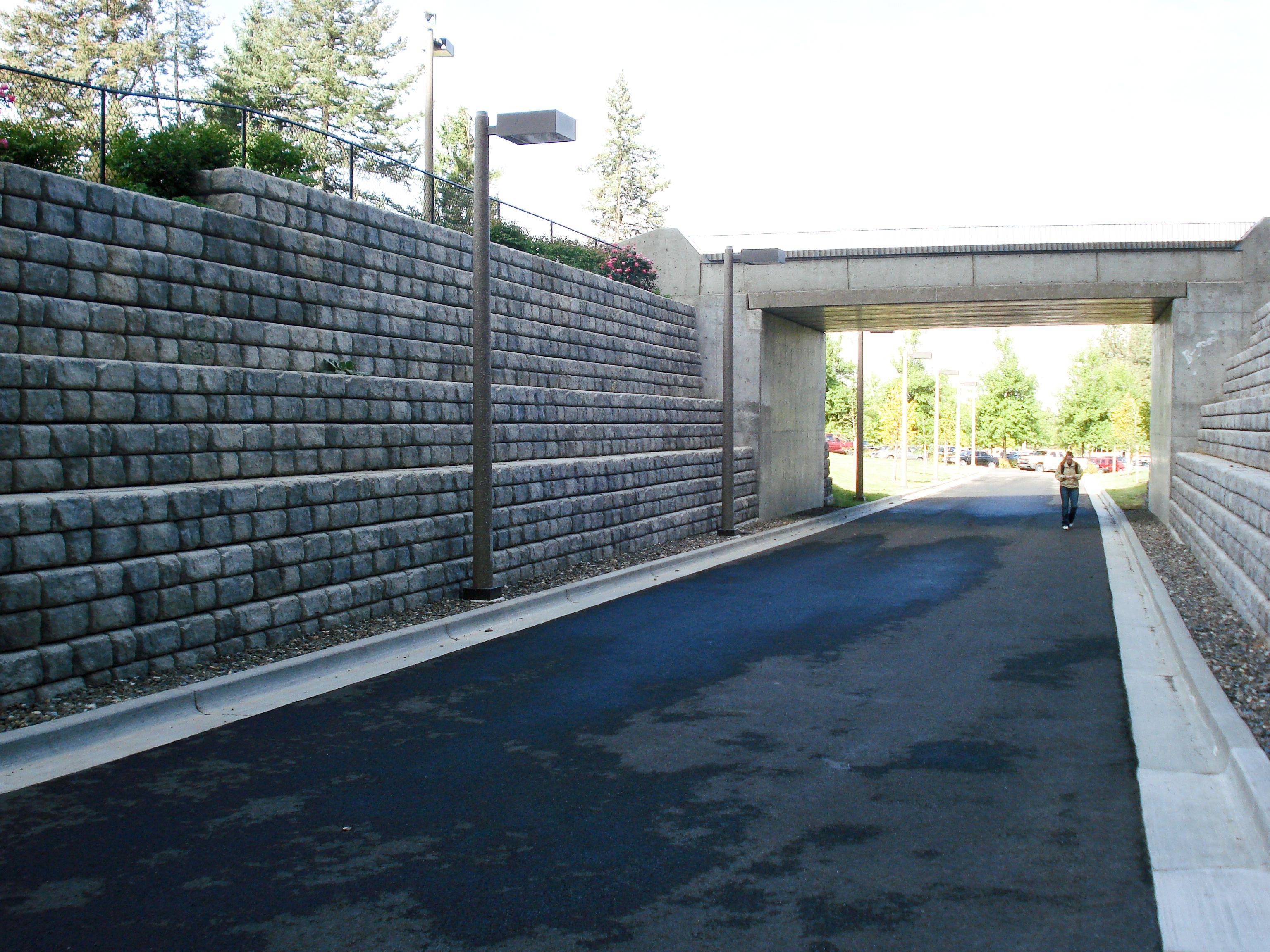 Student walks under overpass and between Cobblestone walls