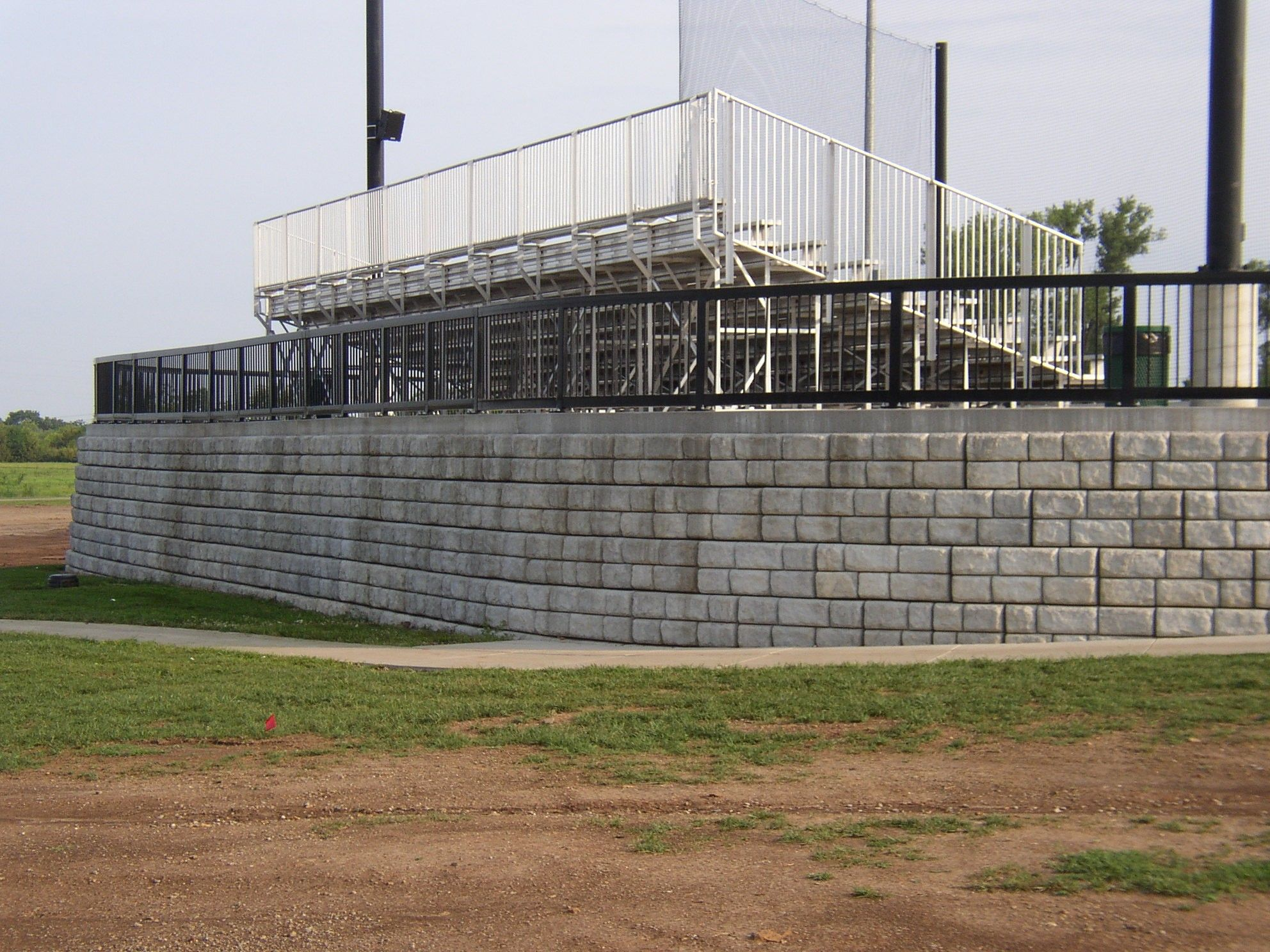 Fenced retaining wall supports bleachers