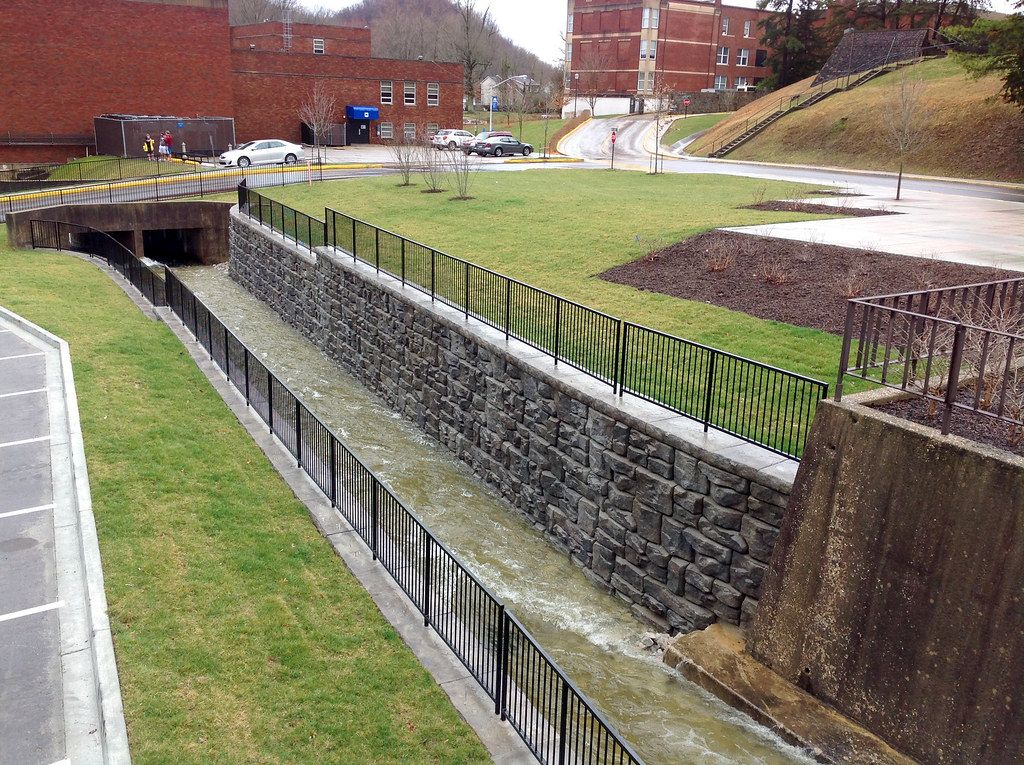 Aesthetic Ledgestone retaining wall supporting storm channel at Morehead State University