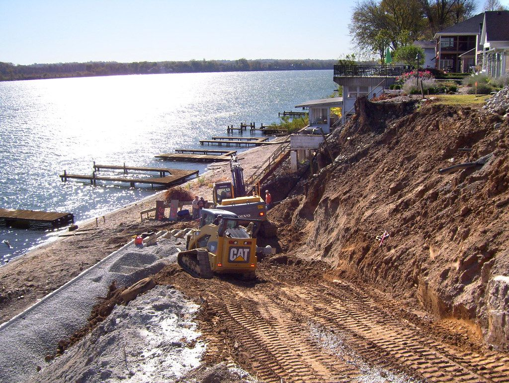 Construction equipment grading land along river in preparation for retaining wall installation