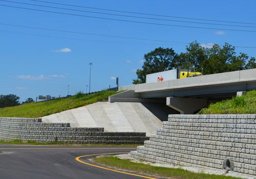 Yellow truck drives on highway supported by Cobblestone retaining walls