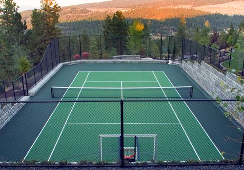 A sport court is ringed with Cobblestone retaining walls