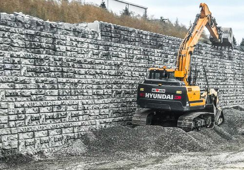 Yellow excavator in front of Redi-Rock XL wall