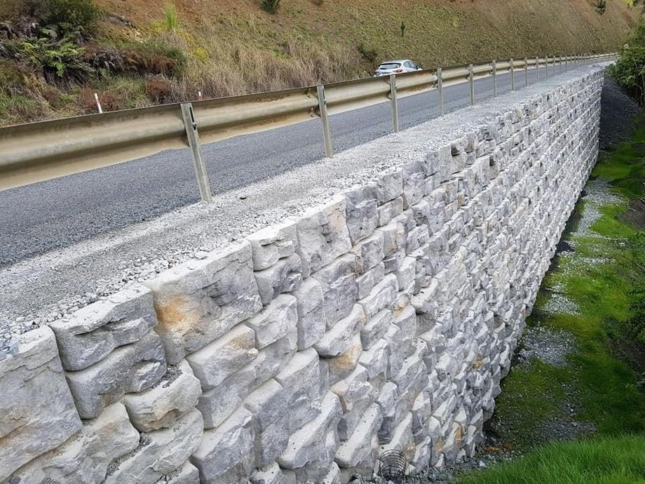 Ledgestone Retaining wall holding up the side of a road with guardrail