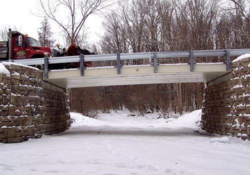 Dump truck driving over bridge with Ledgstone bridge abutments